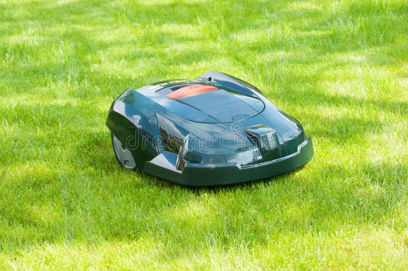 Automatic mower at work. A modern automatic lawn mower on work. The machine is cutting the fresh green grass by itself via gps. Its a self mowing device. Image stock photo