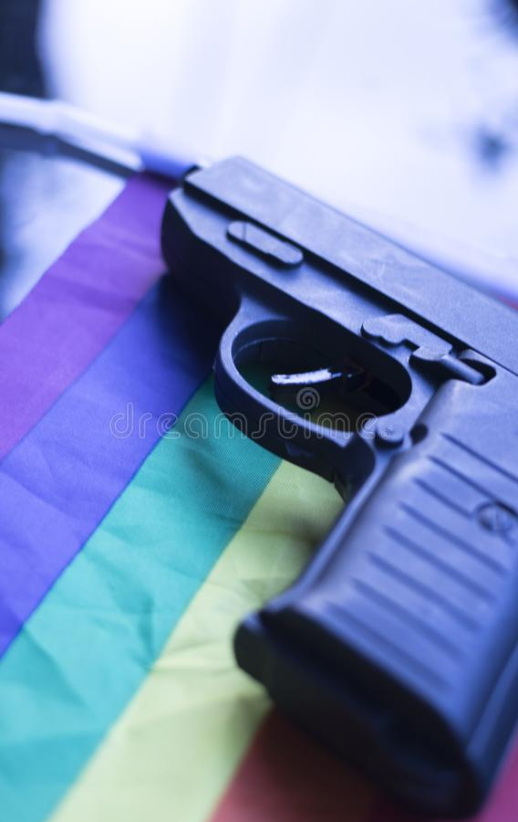 LGBT gay pistol gun. Automatic pistol handgun with gay lesbian LGBT homosexual pride rights flag colors stock images