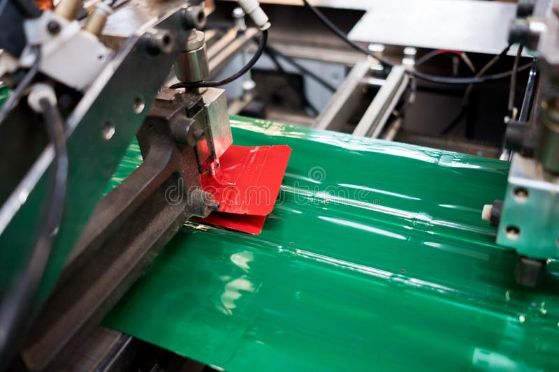 Automatic plastic pouches making and printing  machine in modern factory, plastic packaging is mayor industrial manufacturing stock images