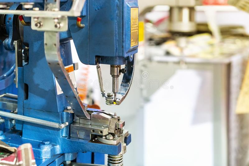 Automatic and precision continuous eyelet punch machine for leather or cloth shoes etc for threading a lace string or rope through. In Manufacturing process in stock images