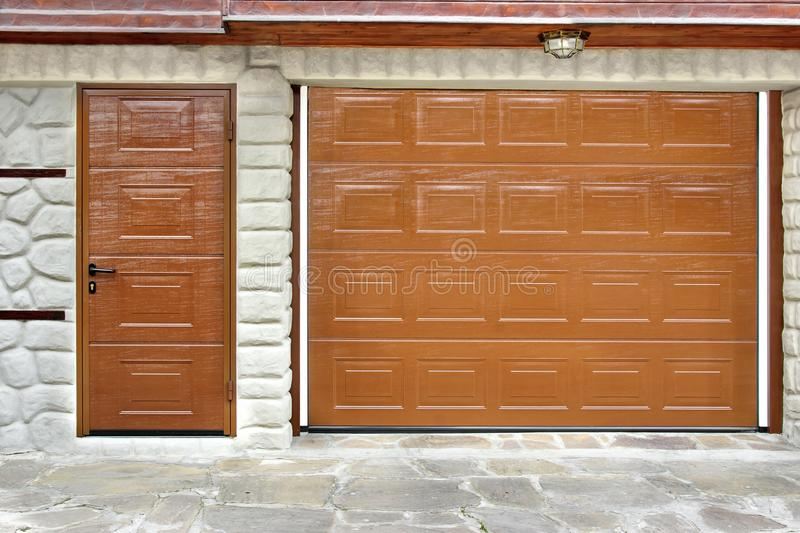 Automatic Roll-up Garage Gate and Door. In White Natural Stone Wall stock photography