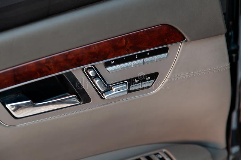 Automatic seat memory buttons on the passenger door panel upholstered in beige light natural leather with a wood element in the royalty free stock image