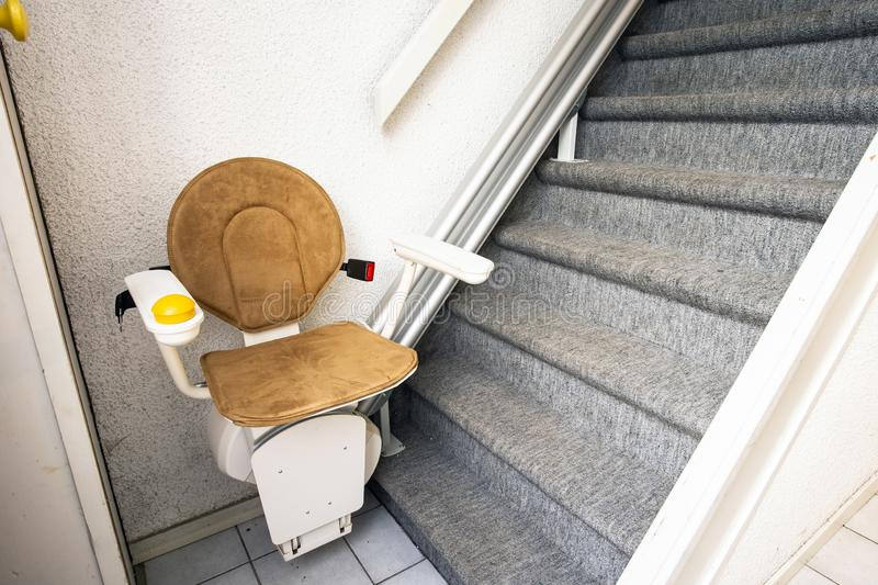 Automatic stair lift on staircase taking elderly people and disabled persons up and down in a house. Close-up royalty free stock photography