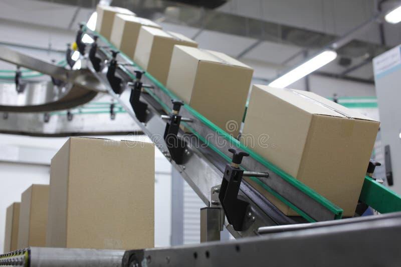 Automation - boîtes en carton sur la bande de conveyeur image stock