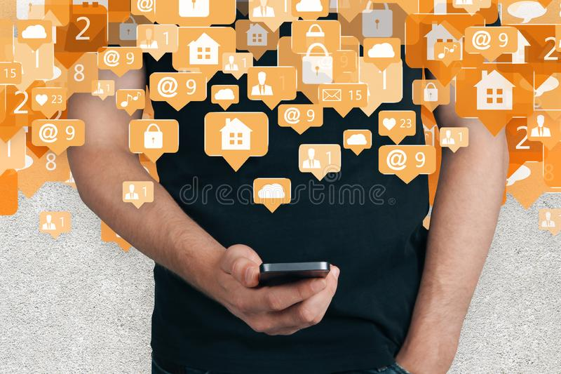 Automation and device concept. Man holding smartphone with abstract house and communication icons on concrete background. Automation and device concept stock photography