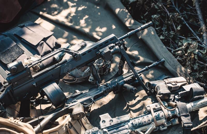 Automatisch, Faustfeuerwaffe, Maschinengewehr, Sturzhelm und Schutzkleidung angehäuft in einem Haufen, liegend aus den Grund stockbild