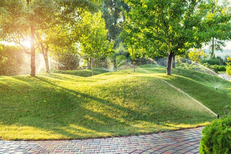 Automatisch tuin het water geven systeem met verschillende die sproeiers onder gras worden geïnstalleerd Landschapsontwerp met ga stock afbeeldingen