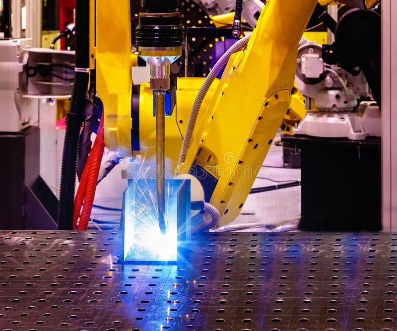 Automatische lassenrobot in moderne fabriek in verrichtingsclose-up van blauwe en gele vlammen met nevel stock afbeeldingen