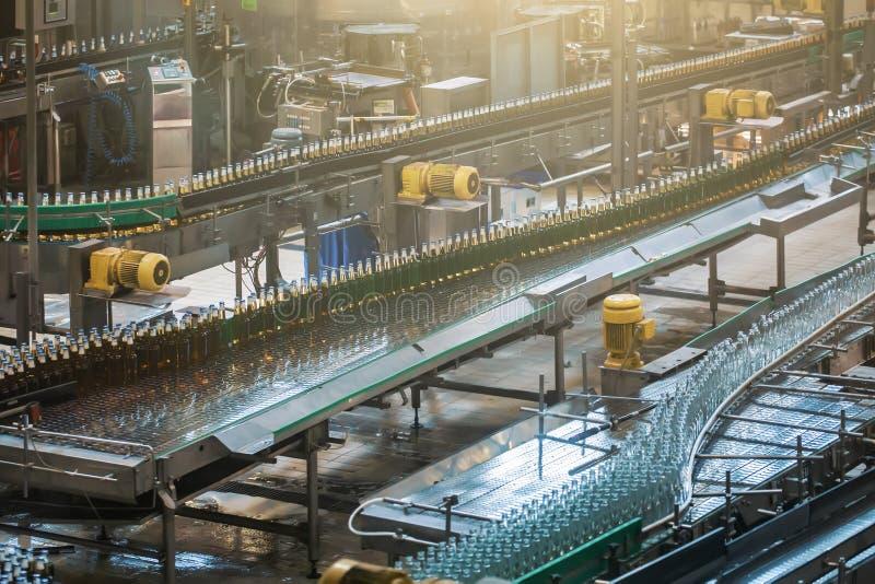 Automatische transportbandlijn of riem met glasflessen bij brouwerijproductie De industri?le machines van het bier bottelende mat stock afbeeldingen