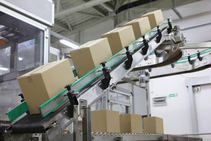 Automatisering - dozen op transportband in fabriek stock afbeeldingen