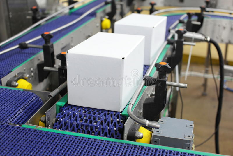 Automatisering - Kartondozen op transportband stock fotografie