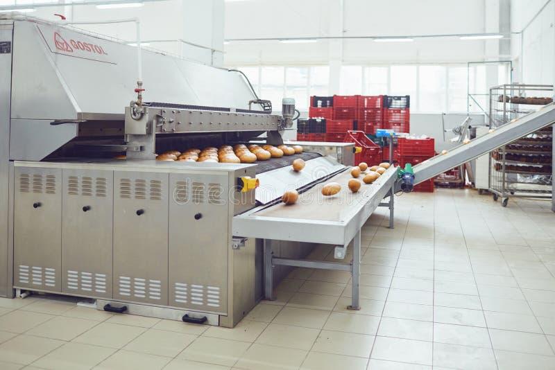 Automatisk bageriproduktionslinje med br?d i bagerifabrik arkivbilder