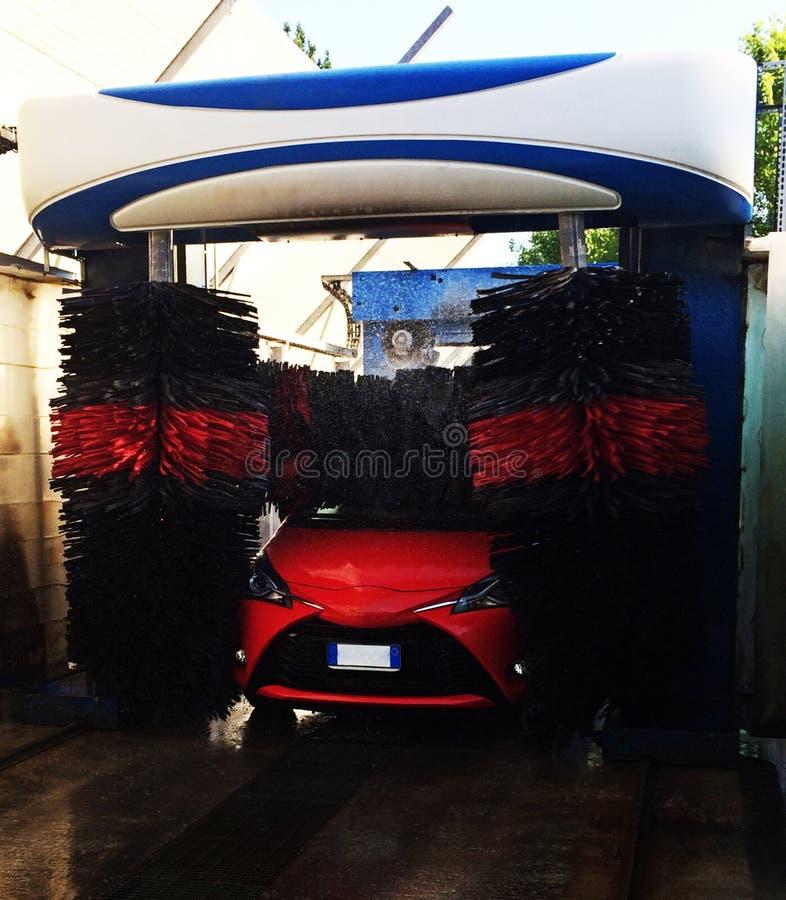 Automatisk biltvätt i handling, tvagningprocess på en röd bil fotografering för bildbyråer