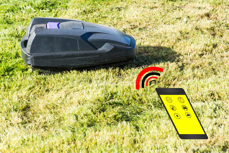 Automatisk gräsklipparekontroll via smartphonen royaltyfri foto