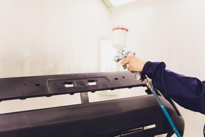 Automatisk m?larf?rg Mekaniker Painting som bilen i auto reparation shoppar royaltyfri bild