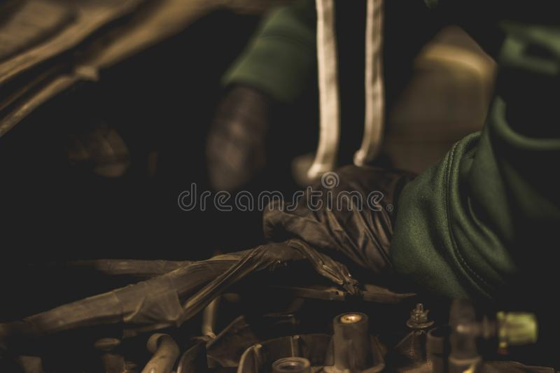 Automatisk mekaniker som arbetar i motorrum av en SUV royaltyfria bilder