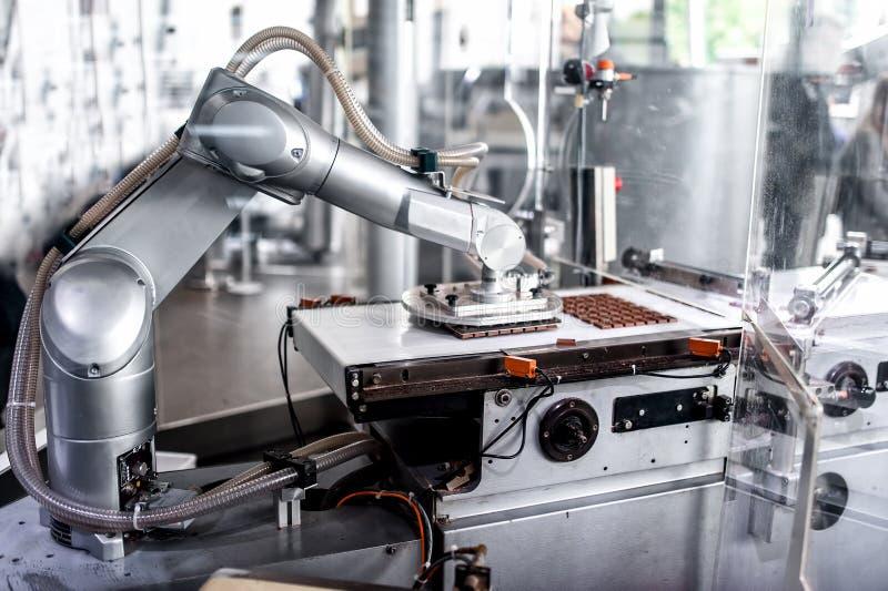 Automatisk robotic hand som flyttar mycket små bitar av choklad royaltyfri fotografi