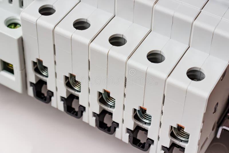 Automatiska strömkretssäkerhetsbrytare med kopplade från portar som installeras på BULLERstången i den vita plast- monterande ask arkivfoto