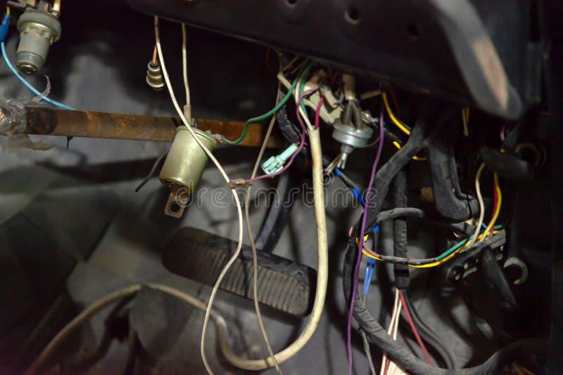 Automatiskt ledningsnät under hjulet av en retro bil för gammal ryss, en demontera instrumentbräda och platser för att reparera o royaltyfri bild