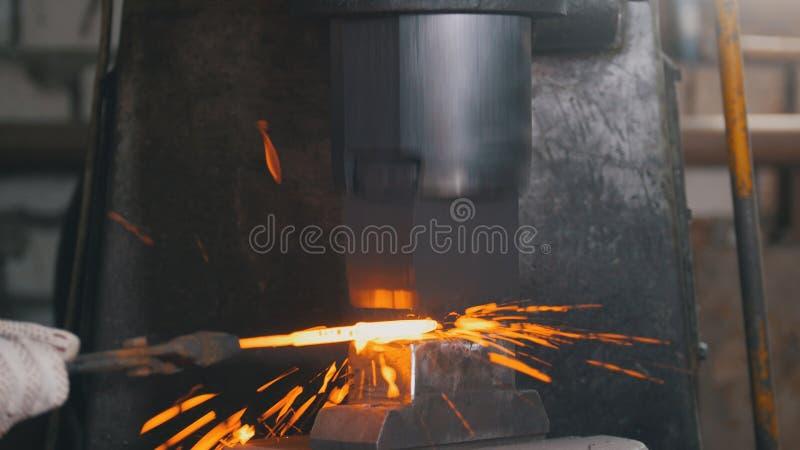 Automatyczny młotkować - blacksmith skucia gorący żelazo na kowadle, krańcowy zakończenie zdjęcia royalty free