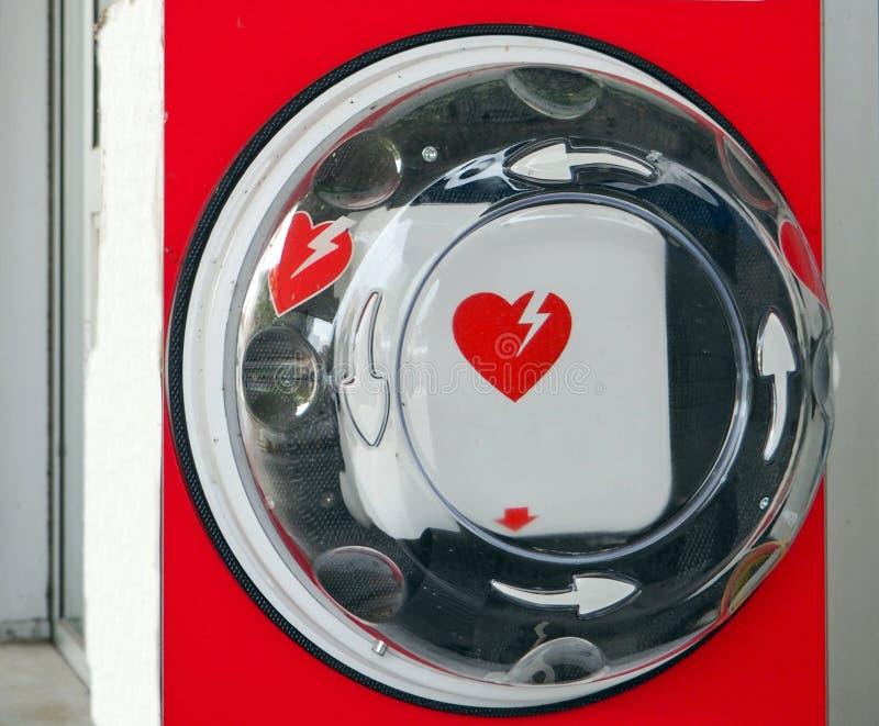 Automatyzujący zewnętrznie defibrillator lub AED, z swój międzynarodowym symbolu obwieszeniem w miejscu publicznym zdjęcie stock