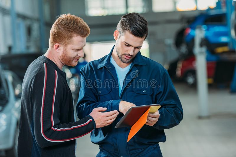 Automechanic and client looking digital tablet. Young automechanic and client looking at the digital tablet at a repair shop stock photos
