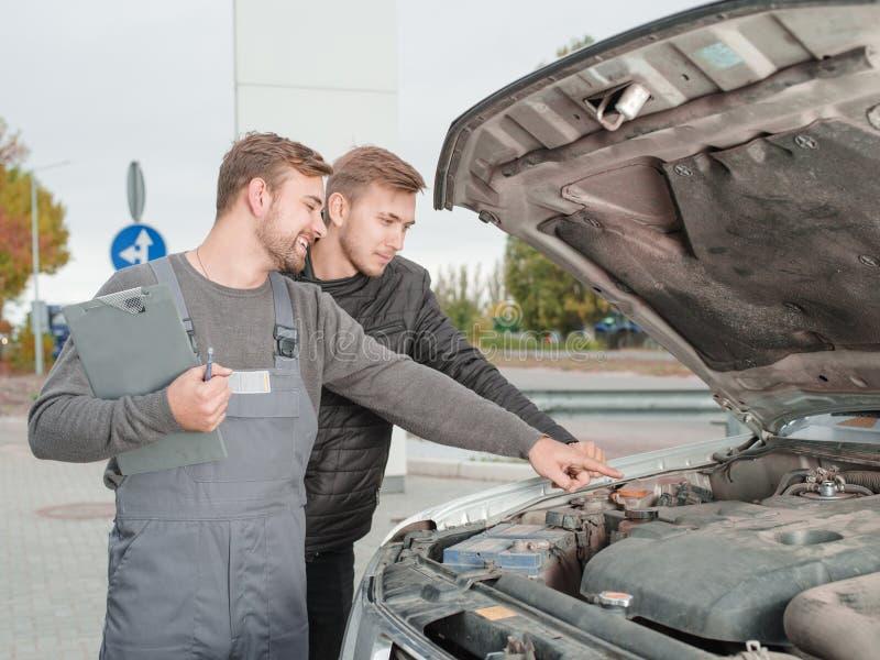 Automechanic ed automobile diagnostica del cliente fuori fotografie stock