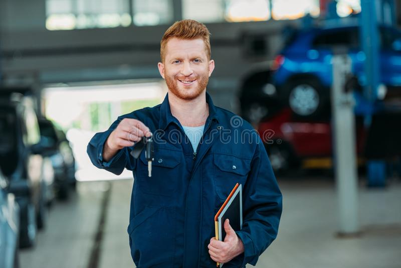 Automechanic holding car keys. And digital tablet at a repair shop stock photos