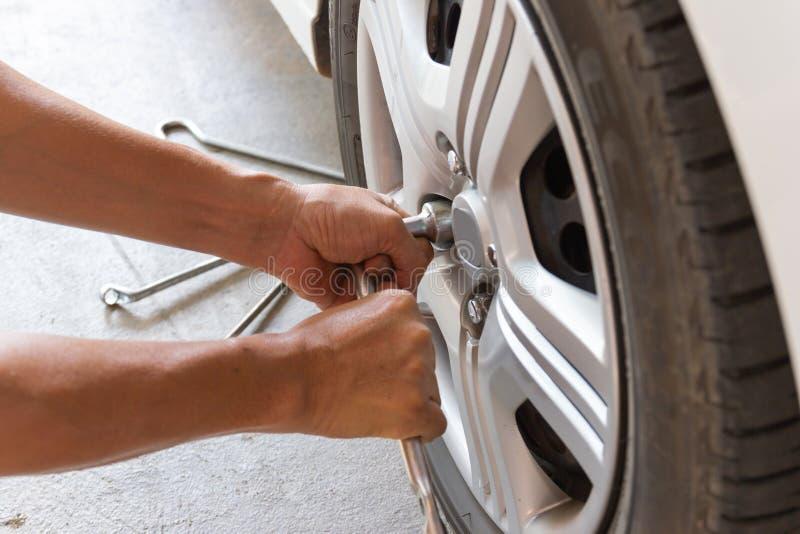 Automechanician het veranderende wiel van de bandauto in autoreparatiewerkplaats stock foto