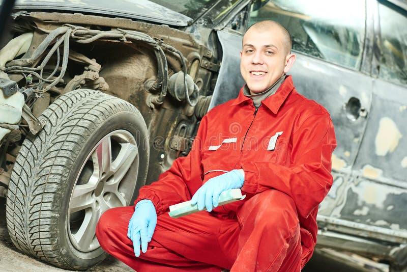 Automechaniker bei der Fahrzeugkarosseriereparaturarbeit lizenzfreie stockfotografie