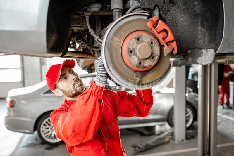 Automechaniker, der Auto am Autoservice bestimmt stockbild