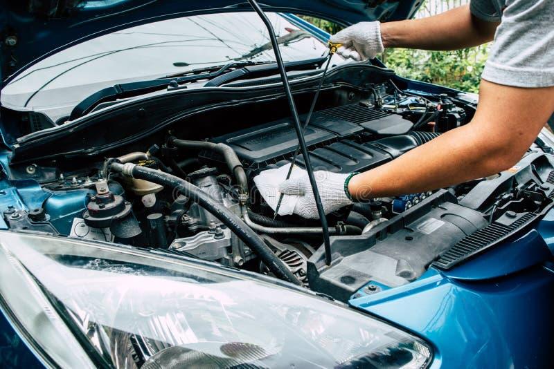 Automechaniker, der den Ölstand im Automotor überprüft stockbilder