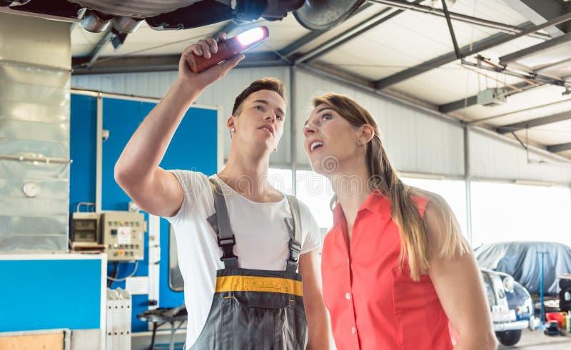 Automechaniker, der die Scheibenbremsrotoren des Autos eines fem überprüft lizenzfreies stockbild