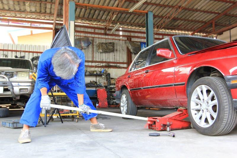 Automechaniker, der Hydraulik-Wagenheber unter das Auto für die Reparatur in Autoreparaturservice einsetzt stockbilder