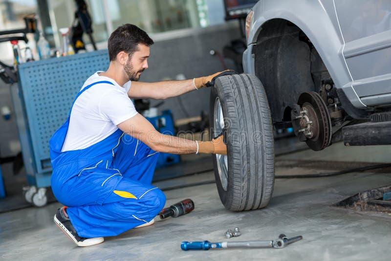 Automechaniker, der Rad eines Autos abmontiert stockbild