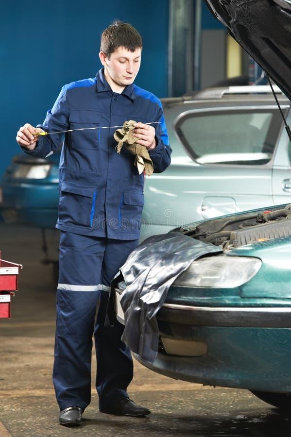 Automechaniker, der Triebwerkölstand prüft lizenzfreie stockfotos