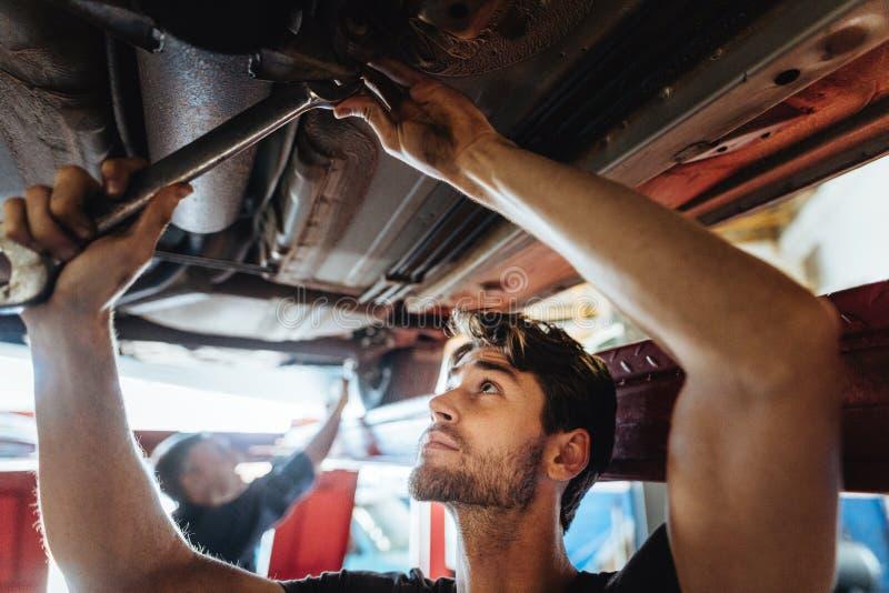 Automechaniker, der unter ein angehobenes Auto arbeitet stockfotografie