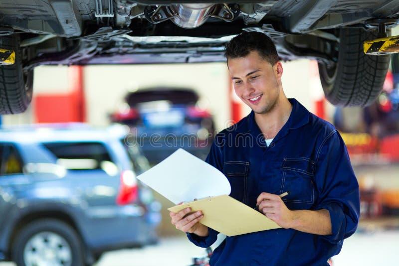 Automechaniker, der an der Unterseite eines Autos arbeitet lizenzfreies stockfoto