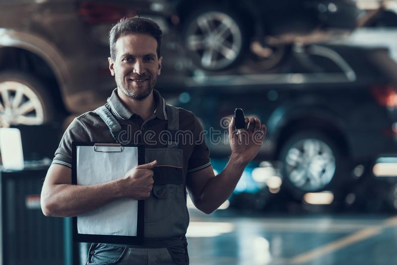 Automechaniker Holding Clipboard und Auto-Schlüssel stockbild