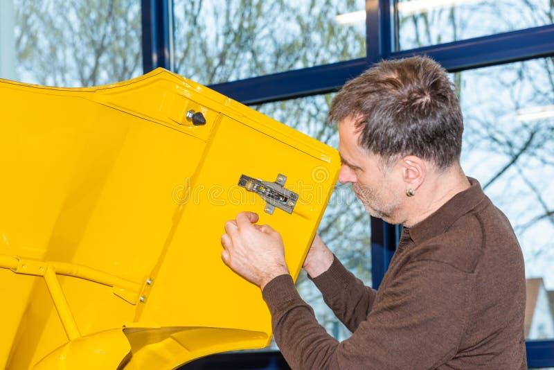 Automechaniker schraubt Autoteile zusammen wieder nach Wiederherstellung - Serie-Reparatur-Werkstatt stockfoto