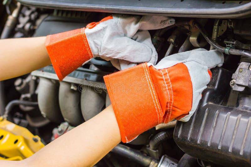 Automechaniker in seiner Reparaturwerkstatt, die nahe bei dem Motor- Abschluss steht lizenzfreies stockfoto