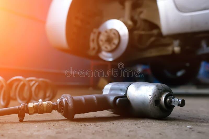 Automechanikermann mit änderndem Reifen des Elektroschraubers draußen Das Auto hob auf den Aufzug und eine Schüssel für Schmieröl lizenzfreie stockfotografie