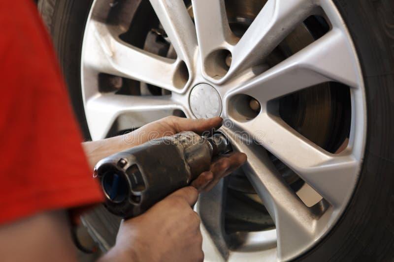 Automechanikermann mit änderndem Reifen des Elektroschraubers draußen Das Auto hob auf den Aufzug und eine Schüssel für Schmieröl stockfotografie