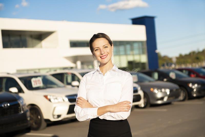 Automiete der jungen Frau vor Garage mit Autos auf dem Hintergrund lizenzfreie stockfotografie