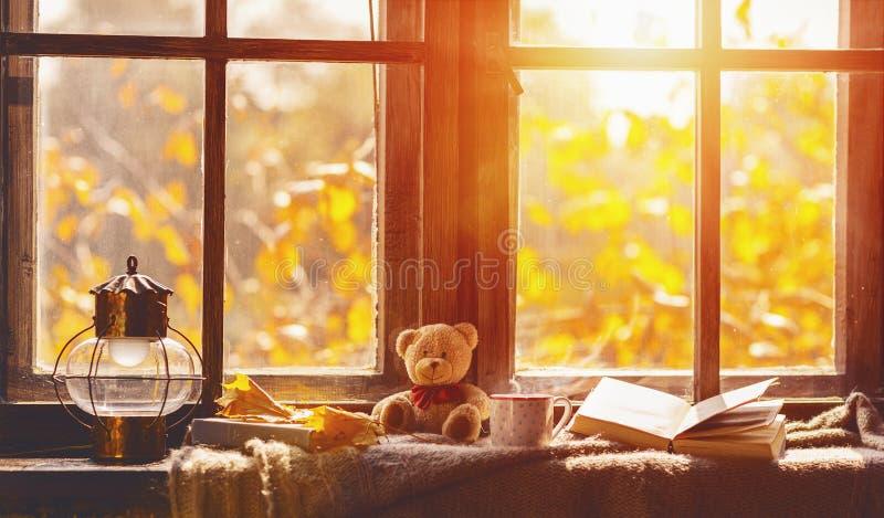 Automne fenêtre confortable avec des feuilles d'automne, livre, tasse de thé images stock