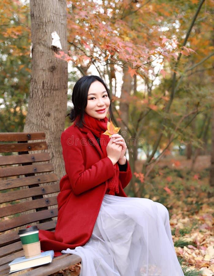 Automne magique, femme d'automne heureuse et bonheur, belle femme s'asseyant sur un banc en parc d'automne photographie stock