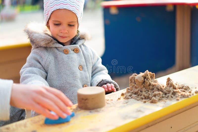 Automne Peu fille faisant des chiffres de sable dans un bac à sable d'enfants photos libres de droits