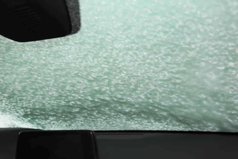 Automobiel die windscherm met schuim wordt behandeld De dienst van de autowasserette royalty-vrije stock afbeeldingen