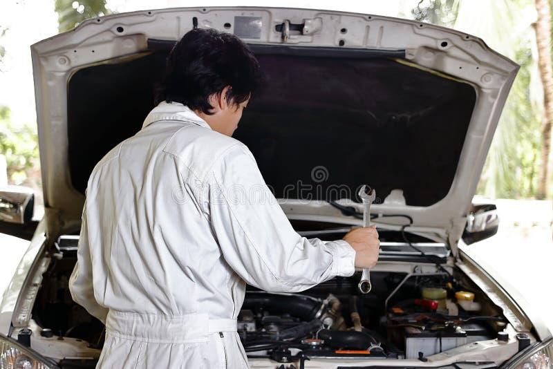 Automobielwerktuigkundige in eenvormig met moersleutel die motor diagnostiseren onder kap van auto bij de reparatiegarage stock fotografie