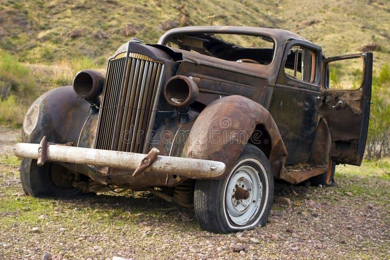 Automobile abbandonata arrugginita in deserto immagini stock libere da diritti